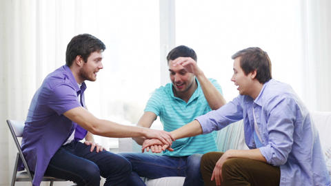 smiling male friends with hands together at home Footage