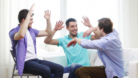 Smiling Male Friends Giving High Five At Home stock footage