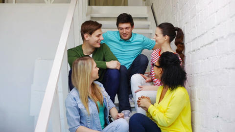 smiling students sitting on stairs and talking Footage