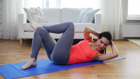 smiling girl doing exercise on mat at home Footage