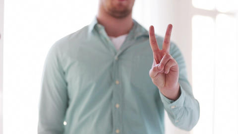 man in shirt showing sign of victory by hand Footage