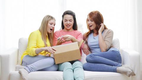 smiling teenage girls opening cardboard box Footage
