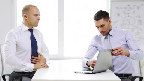 two serious businessmen with laptop in office Footage