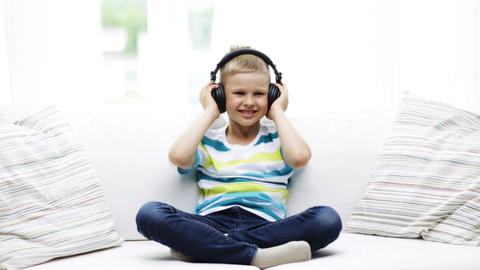smiling little boy in headphones at home Footage