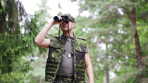 young soldier or hunter with binocular in forest Footage