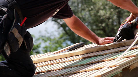 Roofers installing cedar wooden shingle roof Footage