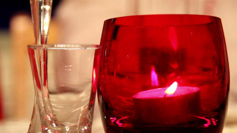 A candlelight inside a red glass and a small glass Live Action