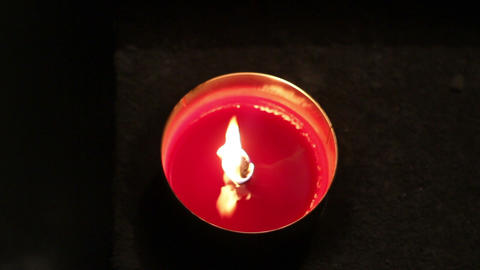 A red melting candle light inside a round glass Footage
