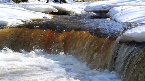 A clear water flowing between the snow-covered are Footage