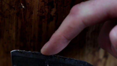 A Mans Finger Is Touching The Blade Of The Axe stock footage
