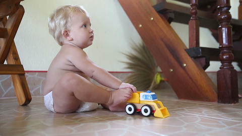 caucasian child plays with cars on the floor near  Footage