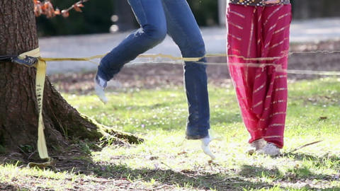 Woman trying to walk on rope and another one is pr Footage