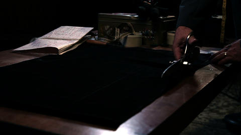 Shot of an old tailor cutting fabric Footage