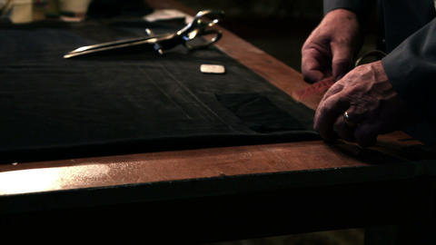 Shot of an old tailor measuring fabric Footage
