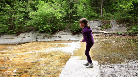 Shot of a little girl throwing stones in water Live Action