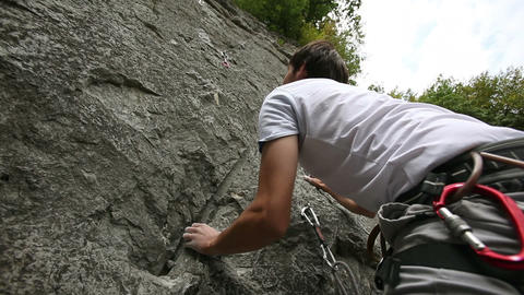 Young man starting to rock climb Footage
