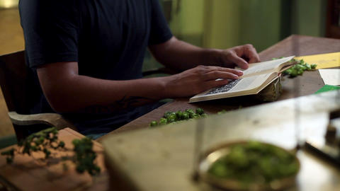 Man reading and looking at the book of herbs Live Action