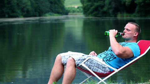 Young man lying in a deckchair near lake and drink Footage