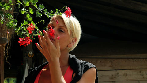 Pretty woman smelling red flowers Footage