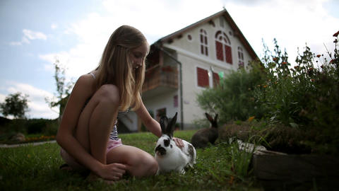 Teenage girl caressing rabbits in front of the hou Footage