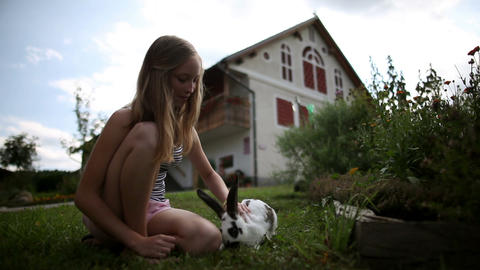 Teenage girl caressing rabbit in front of the hous Footage