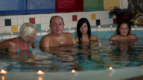 Family in spending free time in a pool with therma Footage