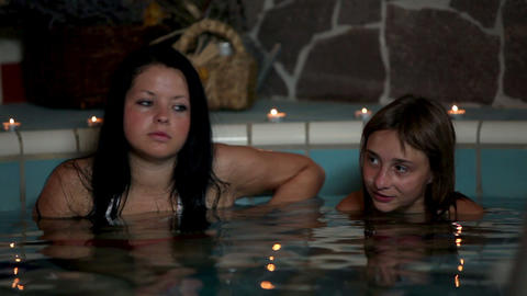 Two girls in a hot pool soaking Footage