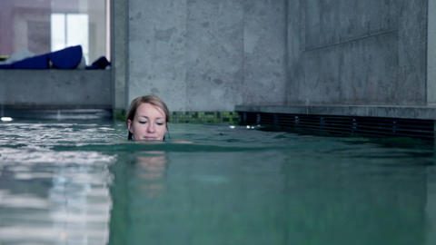 young woman in blue bikini that swimms towards fro Footage