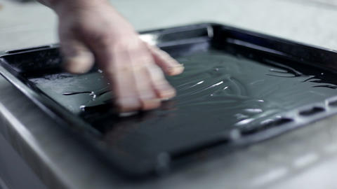black baking sheet that man is greasing with olive Footage