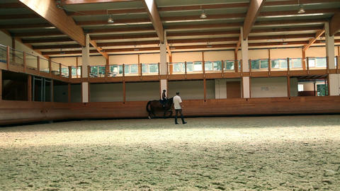 a young girl riding a horse and learning with male Footage