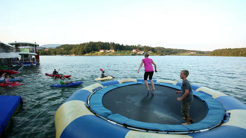 Wide shoot of People jumping on trampoline in wate Footage