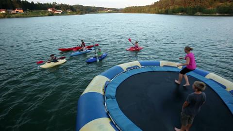 Young people canoeing around trampoline in the lak Footage