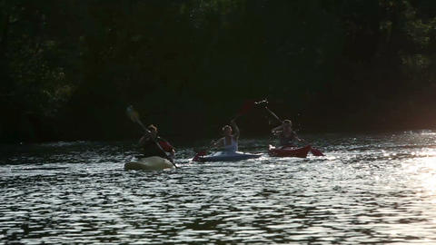Young people canoeing in the lake at sunset Live Action