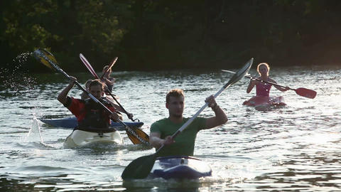 Young boys and girls canoeing by in lake Footage