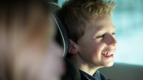 Close up shot of boy making faces in car backseat Footage