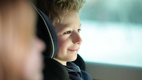Close up shot of boy in back seat of car while fam Footage