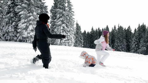 Mother, two children playing with snow Footage