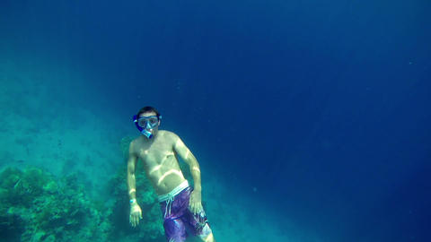 Man with diving equipment swimming up to get some  Footage