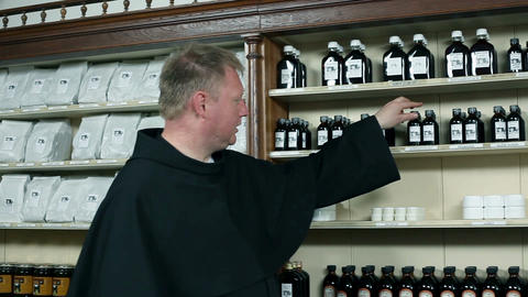 Monk in herb shop selling herbs to customers Stock Video Footage