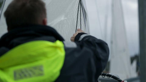 Sailor setting main sail of sailboat early in the  Footage