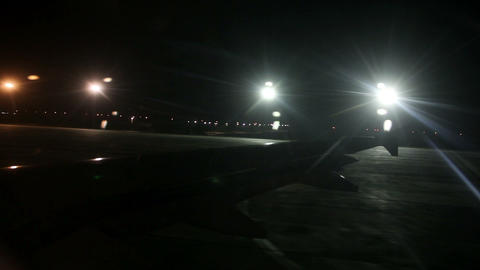 Airplane wing from inside while at airport at nigh Footage