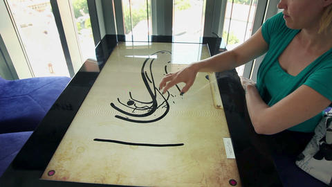 Woman makin creative picture on touch screen table ビデオ