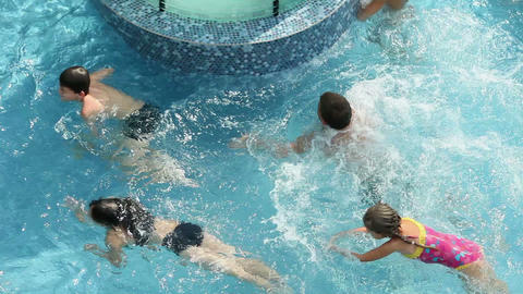 Group of kids jumping into pool to refresh Footage