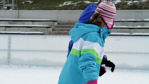 Side shot of two kids skating on ice Footage