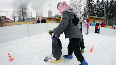 Kid ice skating past obstacles while holding the p Footage