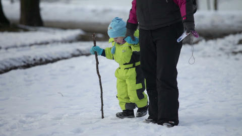 Adult woman walking the small kid dressed in ski j Stock Video Footage