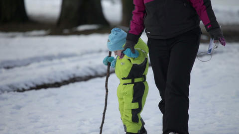 Adult woman walking the small kid dressed in ski j Footage