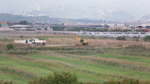 Deep focus shot of trucks and exdcavator Footage