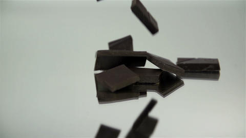 Pieces of chocolate are falling down on the reflec Footage