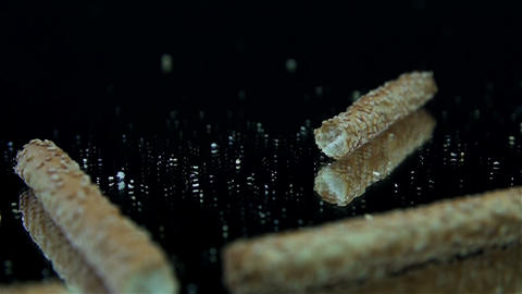 Salty sticks falling on black background in slow m Footage